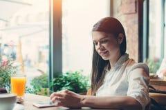 坐在咖啡馆和使用手机的英俊的微笑的妇女键入新的信件,当食用早餐时 免版税库存照片