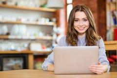 坐在咖啡馆和使用膝上型计算机的美丽的愉快的妇女 免版税库存照片