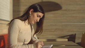 坐在咖啡馆和做在笔记本的年轻深色的妇女笔记 影视素材