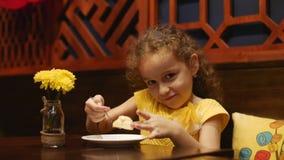 坐在咖啡馆和吃乳酪蛋糕的孩子 关闭 股票录像
