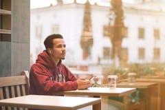 坐在咖啡馆和听的音乐的年轻非洲人从他的手机 免版税库存图片