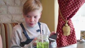 坐在咖啡馆和拿着智能手机的少年 企业咖啡杯方便问题午餐开张了 股票视频