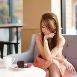 坐在咖啡馆和查看她的新美丽的妇女玫瑰色。   图库摄影