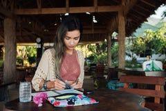坐在咖啡馆和油漆的木桌上的美丽的深色的妇女在册页 库存图片