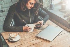 坐在咖啡馆和用途智能手机的木桌上的年轻女商人,当做在笔记本时的笔记 免版税库存照片