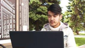 坐在咖啡馆和研究膝上型计算机的亚裔人自由职业者 股票录像