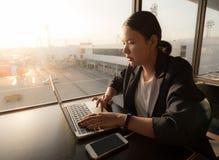 坐在咖啡馆和研究膝上型计算机的女商人,当waiti时 免版税库存图片