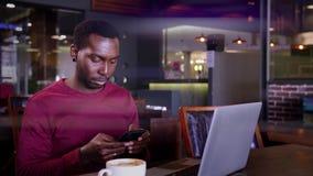 坐在咖啡馆和研究膝上型计算机的愉快的非洲商人画象  股票录像