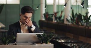 坐在咖啡馆和研究膝上型计算机的疲乏的年轻商人 自由职业者,通信,IT,疲乏的商人 股票录像