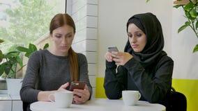 坐在咖啡馆和键入在电话,他们中的一个的两名年轻美丽的妇女hijab的回教妇女,被确定和 股票录像