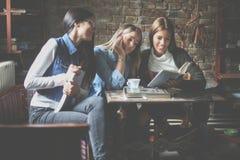 坐在咖啡馆和阅读书的女孩学生 库存照片