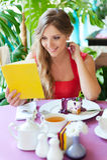 坐在咖啡馆和阅读书的妇女 免版税库存照片