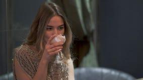 坐在咖啡馆和饮用的鸡尾酒的美丽的年轻女人画象 股票视频