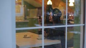 坐在咖啡馆和读的消息的年轻美丽的妇女 股票视频