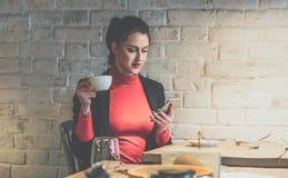 坐在咖啡馆在木桌,饮用的咖啡上和使用智能手机的年轻女实业家 免版税库存照片