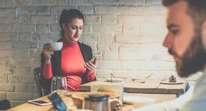 坐在咖啡馆在木桌,饮用的咖啡上和使用智能手机的年轻女实业家 免版税库存图片