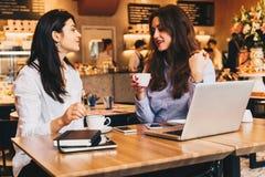 坐在咖啡馆在桌上和使用膝上型计算机,工作的两名年轻女实业家, blogging 学生学习 库存照片