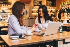 坐在咖啡馆在桌上和使用膝上型计算机,工作的两名年轻女实业家, blogging 图库摄影