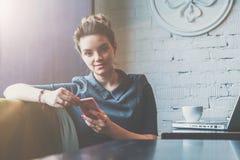 坐在咖啡馆在桌上和拿着智能手机的年轻女商人正面图,当看照相机时 免版税图库摄影