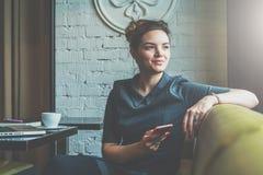 坐在咖啡馆在桌上,倾斜他的在椅子的手后面,看窗口和拿着智能手机的年轻女商人 图库摄影