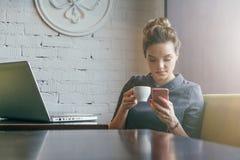 坐在咖啡馆在桌,饮用的咖啡上和使用智能手机的年轻女实业家 免版税库存图片