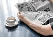 坐在咖啡馆或在家在厨房里的人读书报纸和饮用的咖啡在早晨时间 在黑暗的一个咖啡杯 免版税库存图片