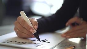 坐在咖啡馆或演播室和写美好的字体词组的年轻女人的手在白皮书 手写,字法 股票录像