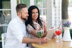 坐在咖啡馆的一对爱恋的夫妇的画象 男人和妇女一起花费时间,观看某事在片剂 库存照片