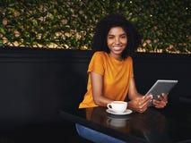 坐在咖啡馆的一微笑的年轻女人的画象 免版税库存图片