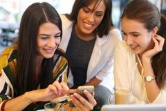 坐在咖啡馆的三个女朋友使用巧妙的电话和 库存照片