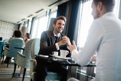 坐在咖啡馆的两个商人谈论项目 免版税库存图片