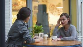 坐在咖啡馆的两个朋友,谈论家庭问题,安慰姐妹的夫人 影视素材