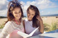 坐在咖啡馆的两名愉快的妇女制表读书菜单外面 免版税库存照片