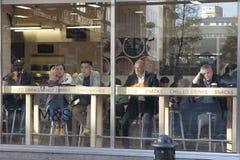坐在咖啡馆的乏味人民,看街道 免版税库存照片