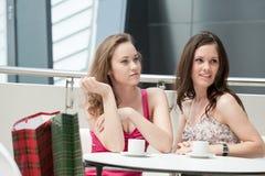 坐在咖啡馆的二个女孩 免版税库存照片