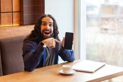 坐在咖啡馆的便装样式的正面惊人的英俊的年轻成人人自由职业者,指向手指倒空屏幕电话, 免版税库存图片