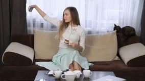 坐在咖啡馆的可爱的少妇吃蛋糕饮用的茶使用触感衰减器和微笑 股票录像
