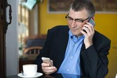 坐在咖啡馆的商人,当打电话和拿着机动性时 免版税库存照片