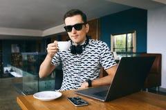 坐在咖啡馆的太阳镜的年轻英俊的行家人,拿着咖啡 膝上型计算机和手机在木桌上 免版税图库摄影