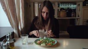 坐在咖啡馆的女性吃沙拉在城市 股票录像