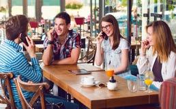 坐在咖啡馆的小组青年人,谈话在电话 库存照片