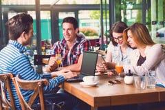 坐在咖啡馆的小组青年人,谈话 免版税图库摄影
