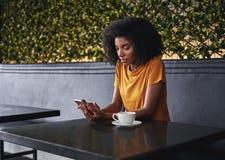 坐在咖啡馆的年轻女人使用手机 免版税库存照片