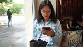 坐在咖啡馆的年轻女人 女孩浏览互联网,聊天,写博克 女性举行的电话和看在他的 影视素材