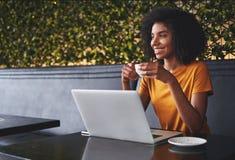 坐在咖啡馆的微笑的年轻女人拿着在手中咖啡杯 免版税库存图片