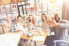 坐在咖啡馆的快乐的国际朋友 免版税图库摄影
