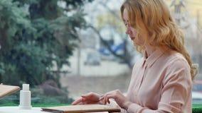 坐在咖啡馆的快乐的少妇拿着菜单拟订发布命令侍者 免版税库存照片