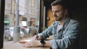 坐在咖啡馆的愉快的人在与笔记本的窗口附近 股票视频