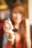 坐在咖啡馆的新美丽的妇女吃巧克力蛋糕 库存图片