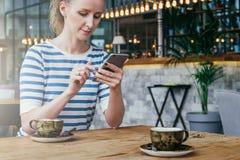 坐在咖啡馆的桌上和使用智能手机的年轻女商人 生活方式 免版税库存图片